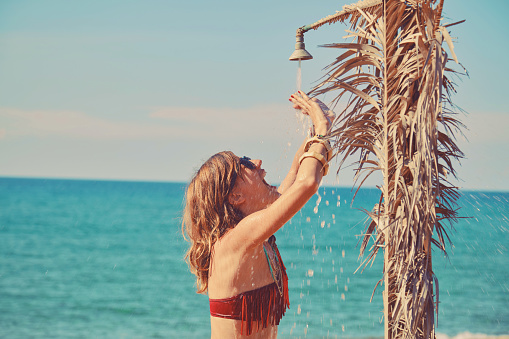 545091450 istock photo Beautiful woman having a shower on the tropical beach. Summer concept. 1168200353