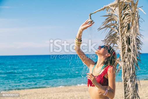 545091450istockphoto Beautiful woman having a shower on the tropical beach. Summer concept. 925200122