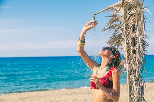 545091450 istock photo Beautiful woman having a shower on the tropical beach. Summer concept. 925200122