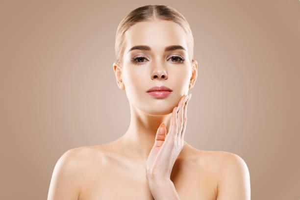 美しい女性健康な皮膚ケア概念の肖像画は、ベージュ色の背景にクローズ アップ。 ストックフォト