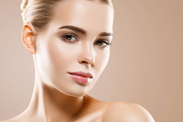 Beautiful woman healthy skin care concept portrait close up on beige background. stock photo