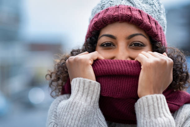 Beautiful woman hiding face in woolen scarf Closeup face of happy african girl holding woolen scarf with hands over nose to protect from the frost. Portrait of beautiful young black woman in warm winter knitted clothes covering her face and looking at camera. warm clothing stock pictures, royalty-free photos & images