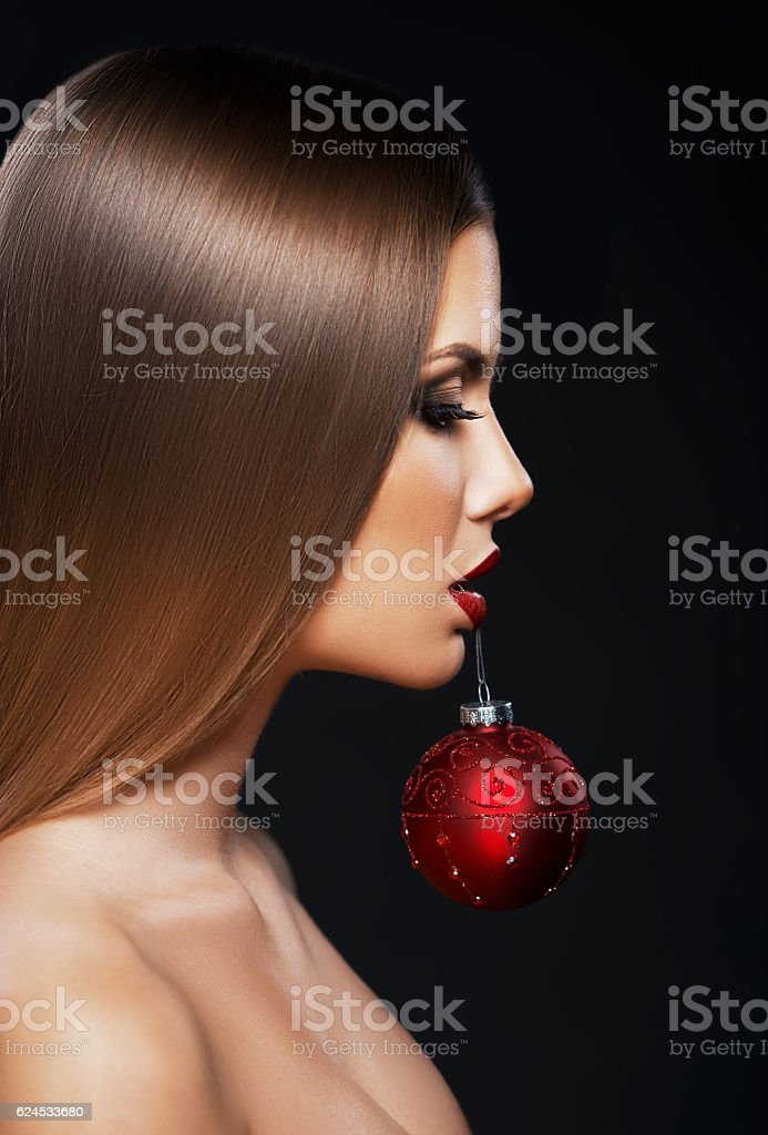 Beautiful woman holding a Christmas ornament with teeth stock photo