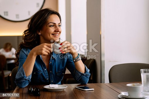 istock Beautiful woman holding a cup of coffee. 847321732