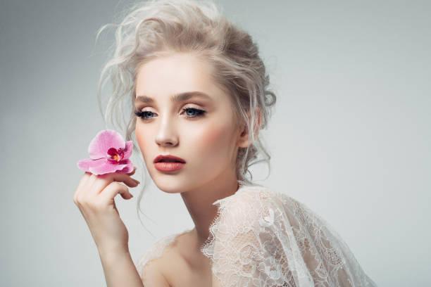 Bir çiçek tutan güzel kadın stok fotoğrafı