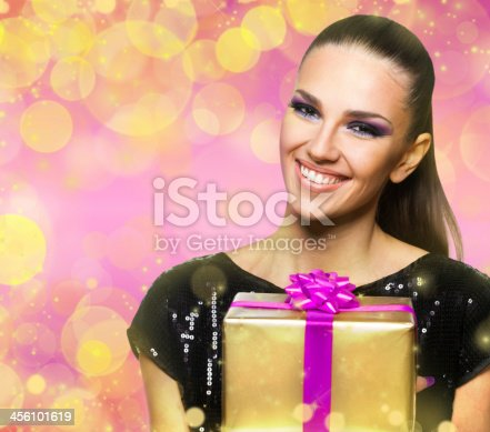 455111881istockphoto Beautiful woman holding a  gift over colorful shiny background 456101619