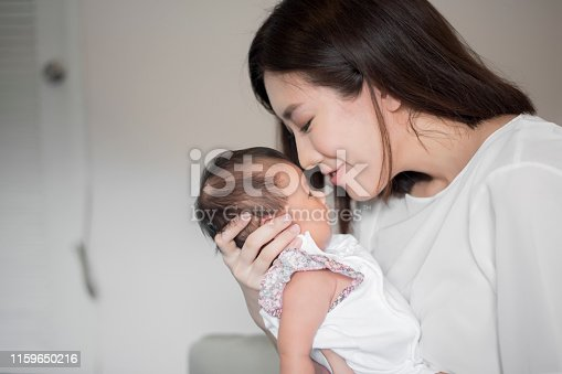 istock Beautiful woman holding a newborn baby in her arms 1159650216
