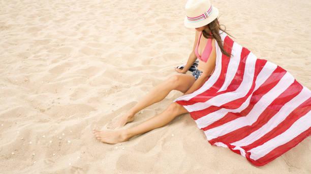 Linda mulher segurando uma bandeira americana na praia - foto de acervo