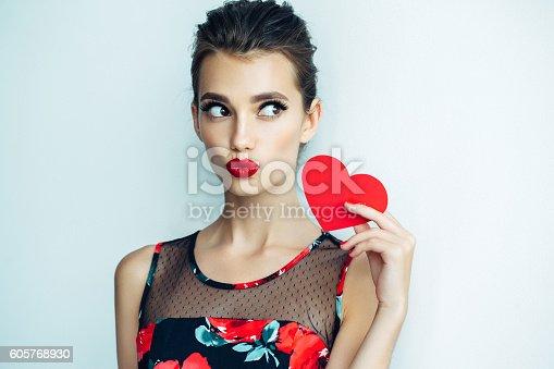 istock Beautiful woman holding artificial heart 605768930