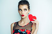 Studio shot of young beautiful woman holding artificial heart. Professional make-up and hairstyle.