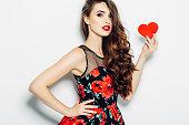Beautiful woman holding artificial heart