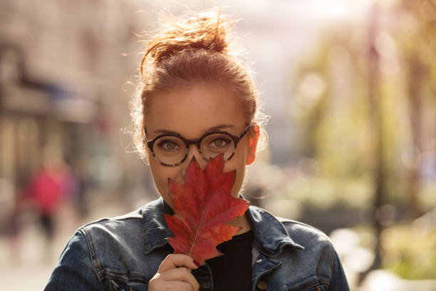 Beautiful woman holding autumn leaf on the street. Autumn concept. stock photo