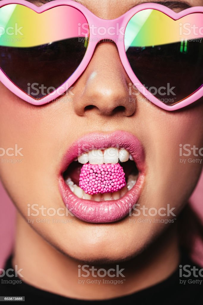 Beautiful woman holding candy in mouth stock photo