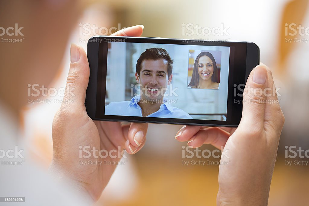 Beautiful woman holding cell phone during a skype video stock photo