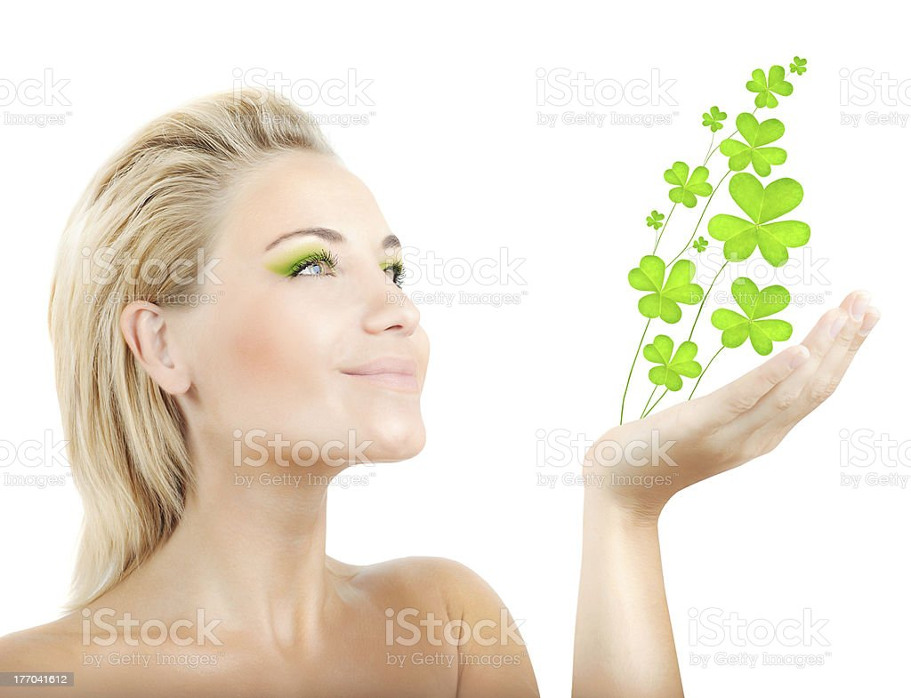Beautiful woman holding clover leaves stock photo