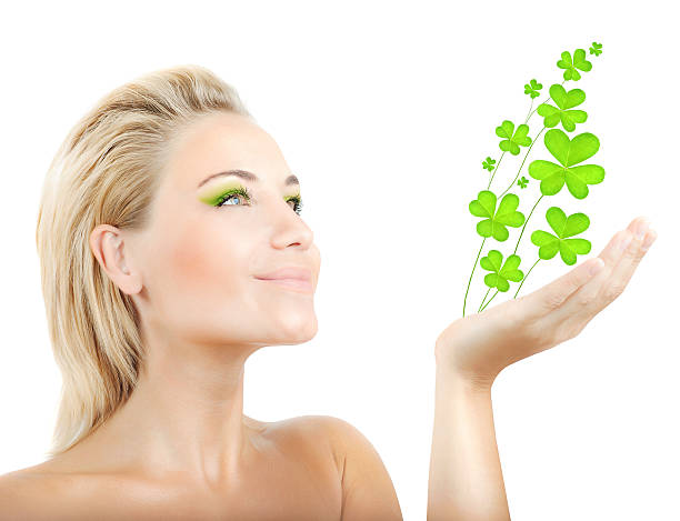 beautiful woman holding clover leaves - luck of the irish stock photos and pictures