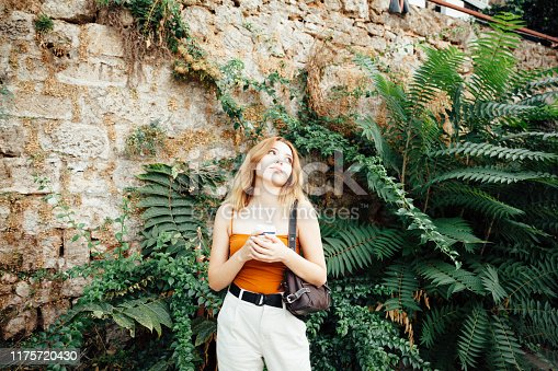 531098549istockphoto Beautiful woman holding coffee cup 1175720430