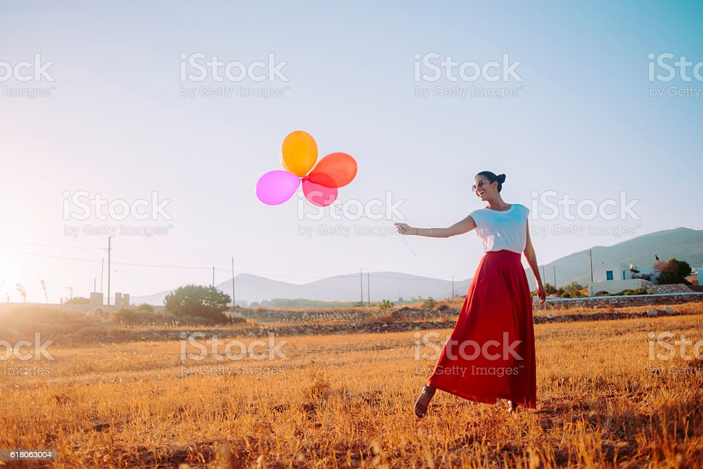beautiful woman holding colorful balloons in the field stock photo