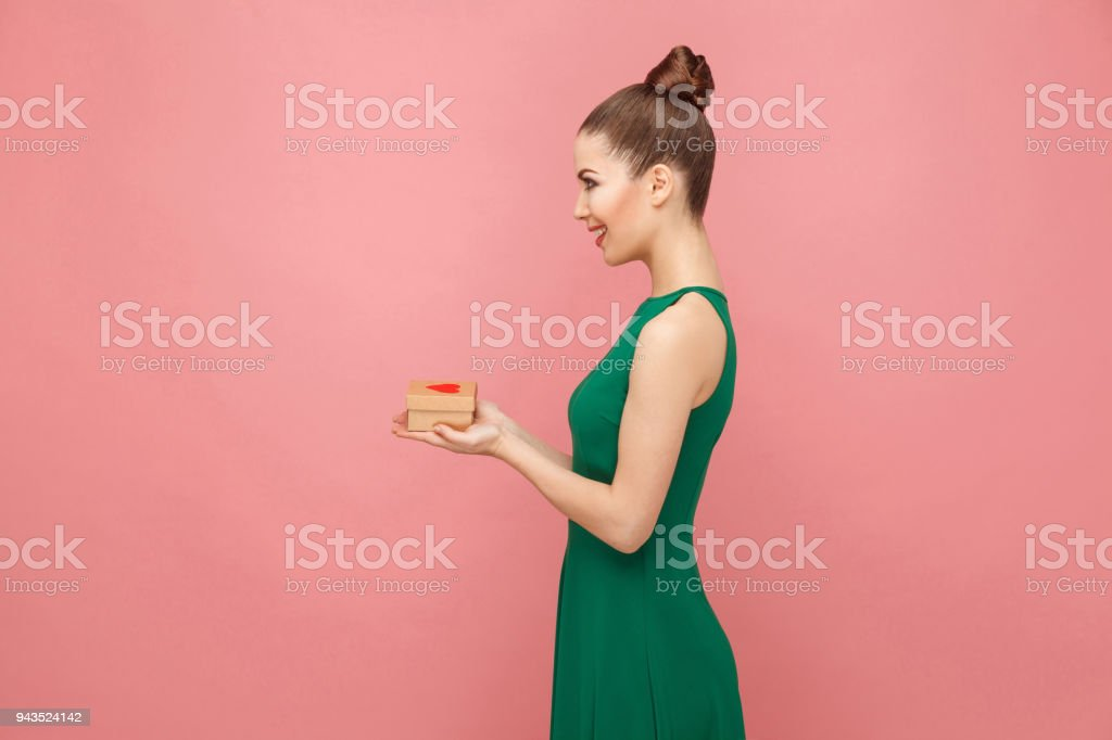 Beautiful woman holding gift box with hearts, toothy smiling stock photo