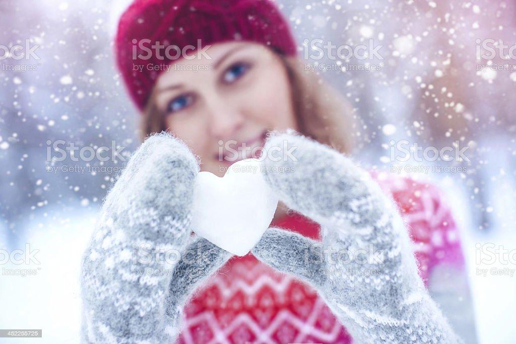 Beautiful woman holding heart-shaped snowball stock photo