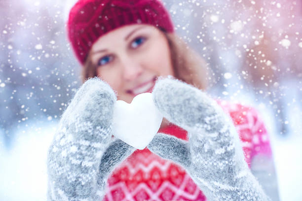 Beautiful woman holding heart-shaped snowball stock photo