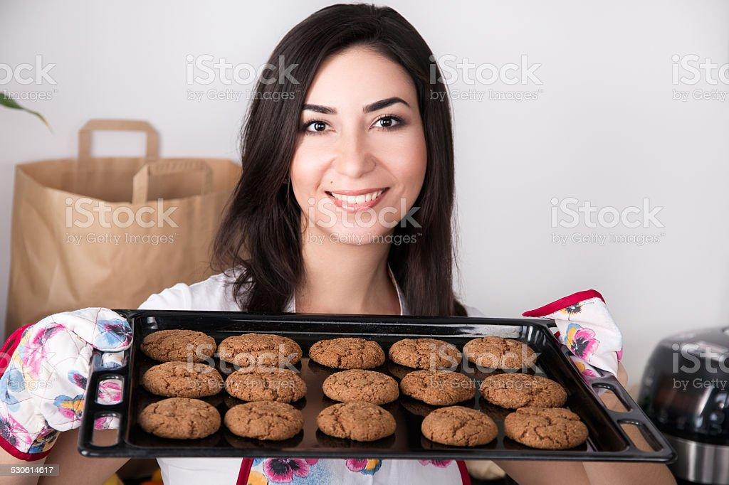 Linda mulher segurando quente de Assadeira com os'cookies' - fotografia de stock
