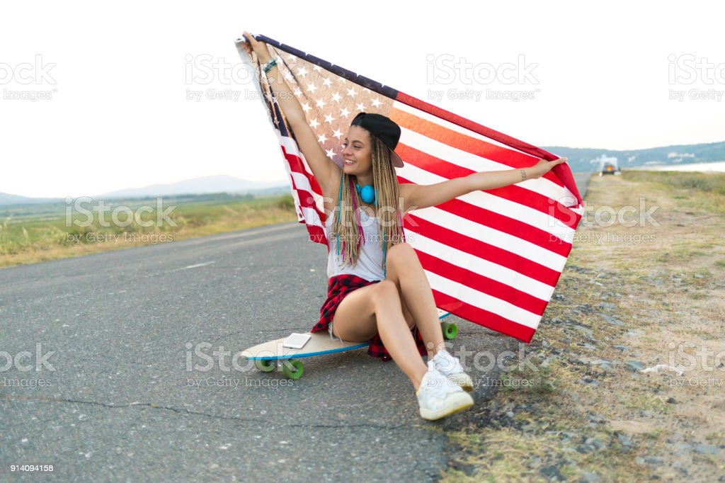Beautiful woman holding national flag on country road stock photo