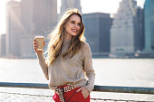 Beautiful woman holding paper coffee cup walking in the city