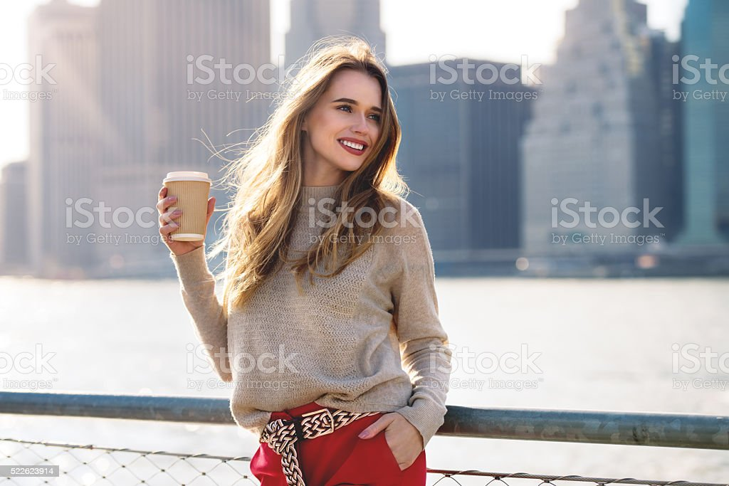 Beautiful woman holding paper coffee cup walking in the city stock photo