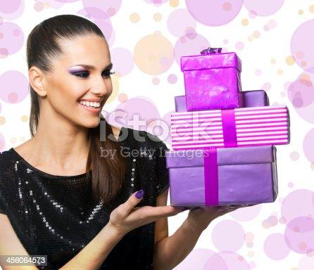 455111881istockphoto Beautiful woman holding purple gifts 456064573