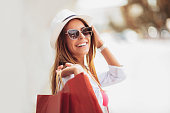 Beautiful woman holding shopping bags and smiling - outdoors