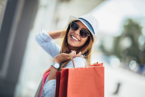 Beautiful woman holding shopping bags and smiling - outdoors stock photo