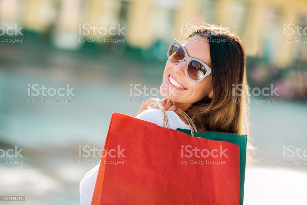 Hermosa mujer sosteniendo bolsas de la compra y sonriendo-aire libre - foto de stock