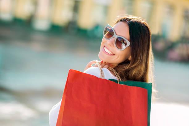 linda mulher segurando sacolas de compras e sorrindo ao ar livre - dia do cliente - fotografias e filmes do acervo
