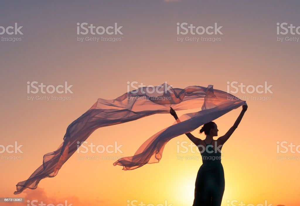 Beautiful woman holding silk cloth in the wind - Photo