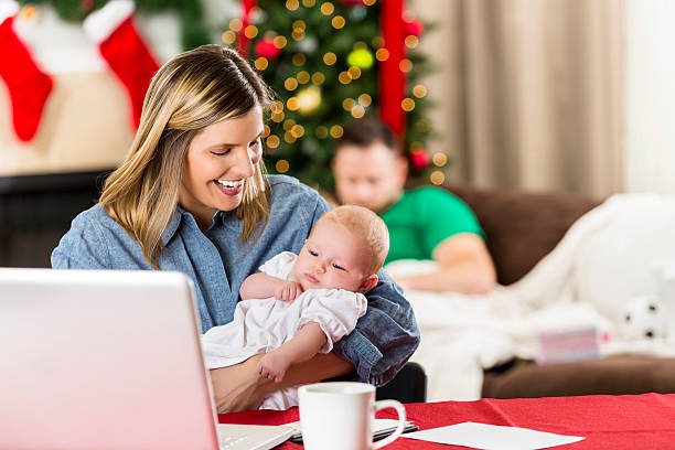 beautiful woman holds baby while paying christmas bills - holiday and invoice family foto e immagini stock