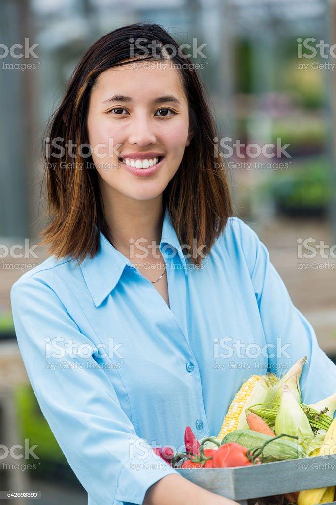 Beautiful woman holds basket full of fresh veggies stock photo