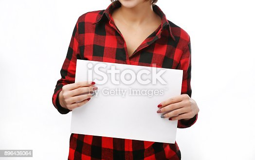 istock Beautiful woman holds out a blank A4 card. Isolated on white background. Red headed girl. Space for text 896436064