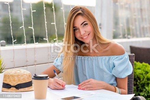 istock Beautiful woman in a blue dress, girl in summer. Fills a paper contract, puts a list on the contract. Long hair everyday makeup. Happy smiling. Ball pen in hand, writes text on a piece of paper. 1148070402