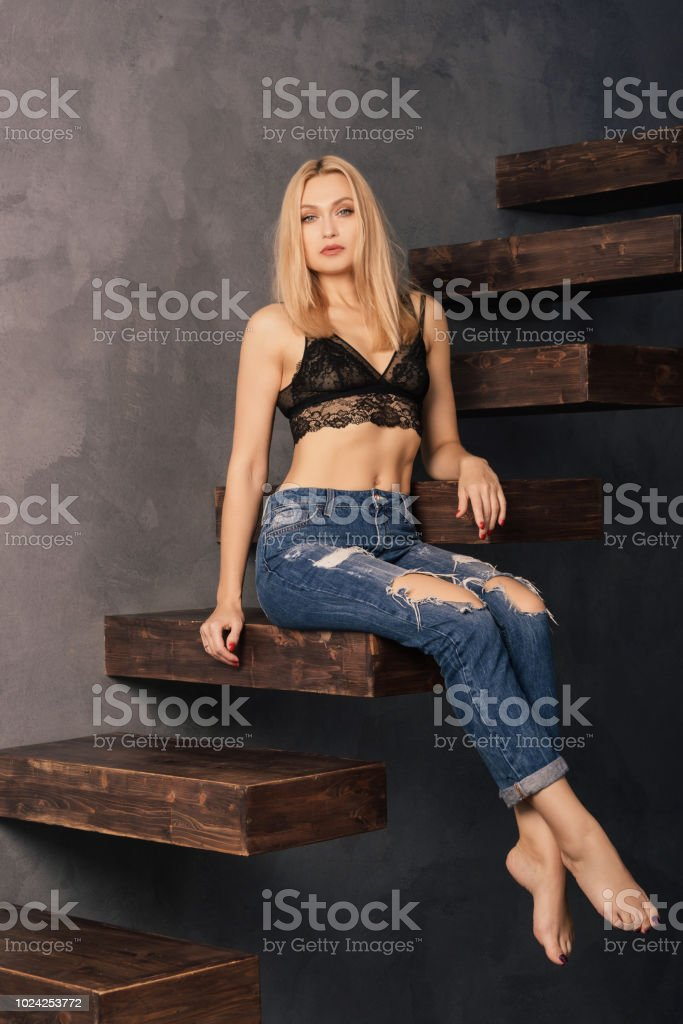 beautiful woman in a bra and jeans posing on a wooden cantilever stairs stock photo
