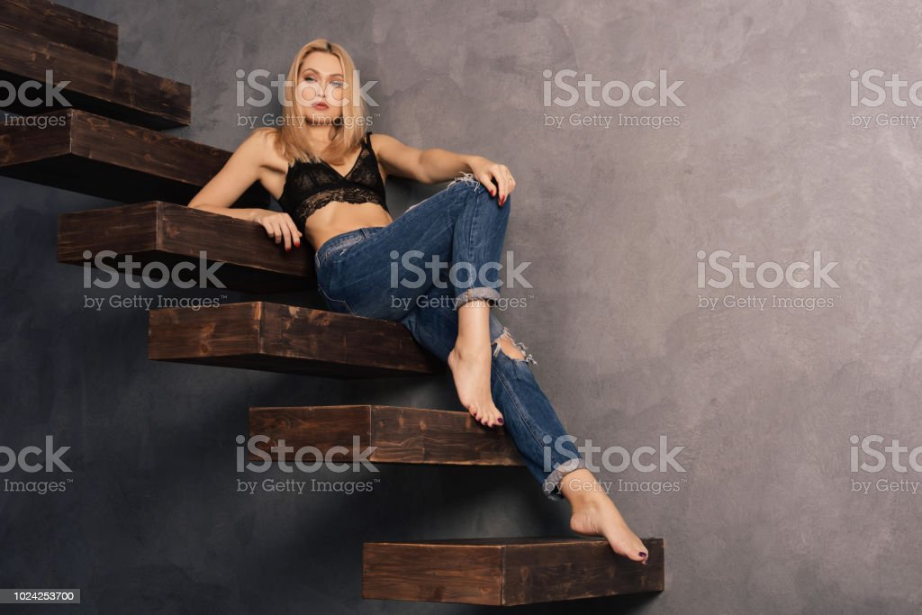 beautiful woman in a bra and jeans relaxes on a wooden cantilever steps stock photo