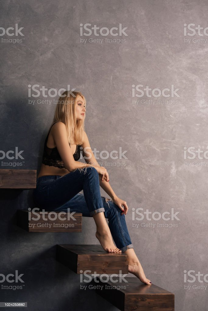 beautiful woman in a bra and jeans sits on a wooden cantilever steps stock photo