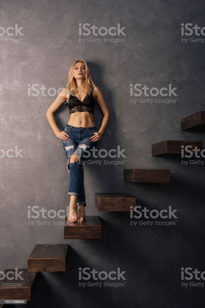 beautiful woman in a bra and jeans standing on a wooden cantilever steps stock photo