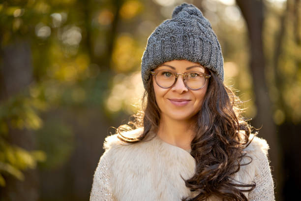 beautiful woman in a cap and glasses on a background of autumn forest