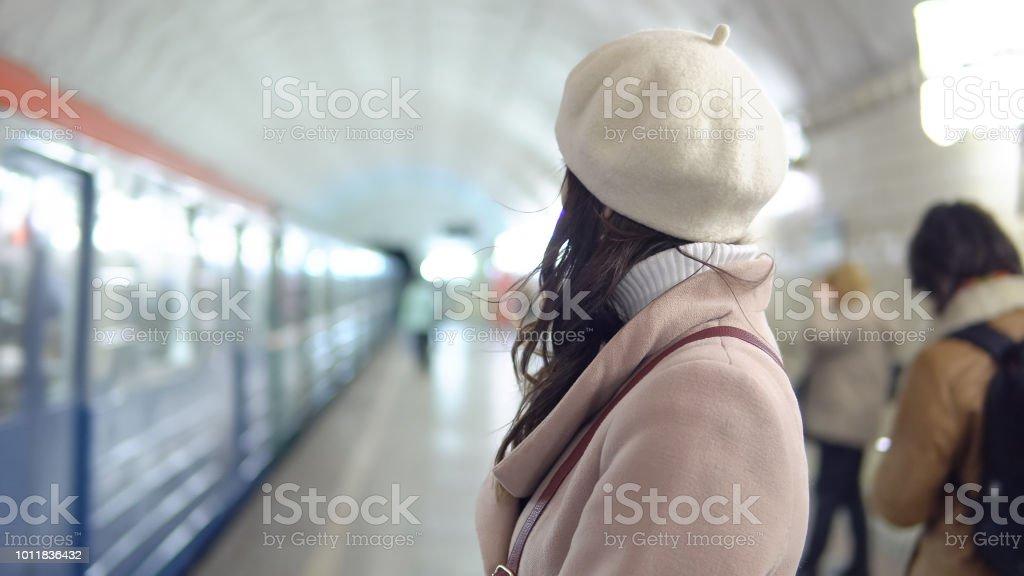 Schöne Frau in einem Mantel in Metropiliten warten auf einen Zug – Foto