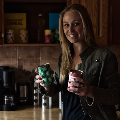 Beautiful woman in a darkened kitchen, possibly during a power outage, decides on canned food