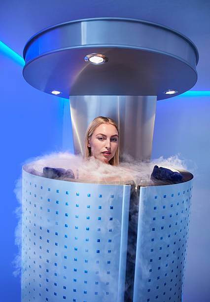 Beautiful woman in a full body cryotherapy camber Portrait of beautiful young woman in a full body cryotherapy camber at cosmetology clinic. She is undergoing skin treatment using cold nitrogen vapors. cryotherapy stock pictures, royalty-free photos & images