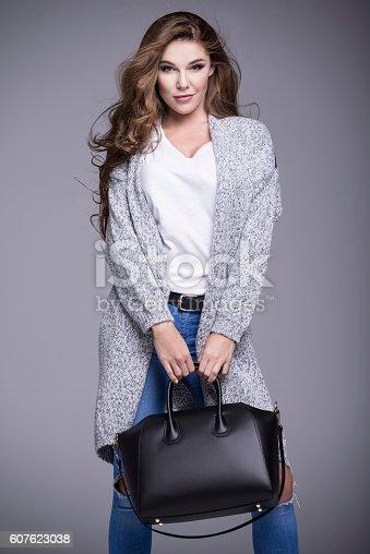 istock Beautiful woman in a gray sweater and a black handbag 607623038