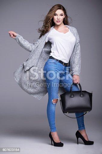 istock Beautiful woman in a gray sweater and a black handbag 607623154