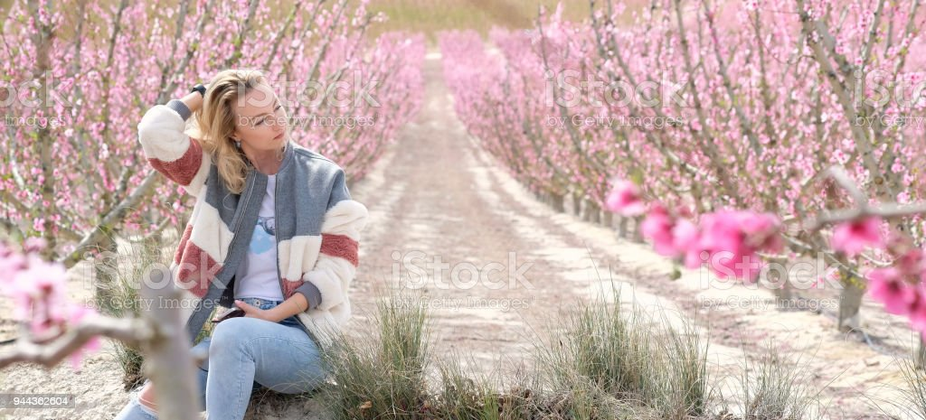 Beautiful woman in a grove of fruit trees stock photo